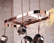 Hanging solid copper pot rack with pans hanging from copper hooks
